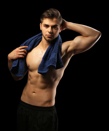 Muscle young man holding towel on dark background Stock Photo