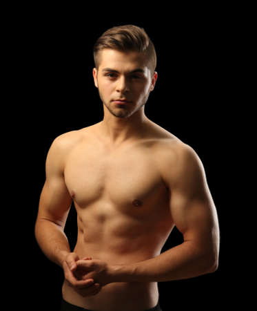Muscle young man on dark background