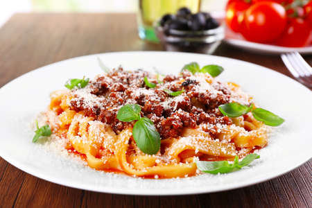 Pasta Bolognese with parmesan and basil on table close up Stock Photo