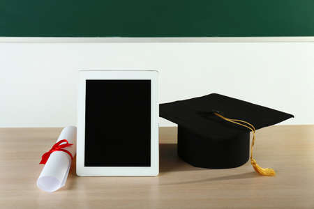 Graduation cap with tablet and diploma on table in class 写真素材