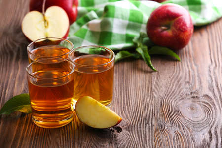 Glasses of apple juice and fruits on table close up