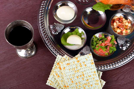 Matzo for Passover with Seder meal with wine on plate on table close up