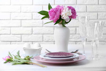 Beautiful table setting with flowers in vase on brick wall background Stock Photo