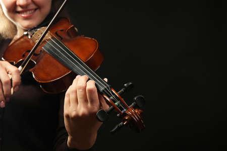 Violinist playing violin on dark background