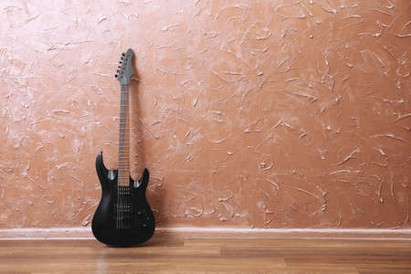 Electric guitar on brown wall background