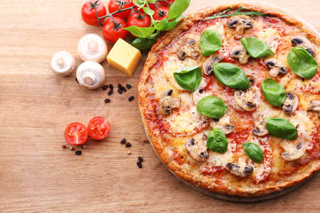 Tasty pizza with vegetables and basil on table close up Stock Photo