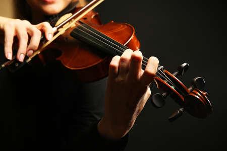 暗い背景にバイオリンを弾くヴァイオリニスト
