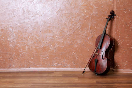 Classical cello and bow on brown wall background Stock Photo