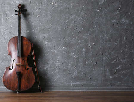 Classical cello and bow on gray wall background 版權商用圖片