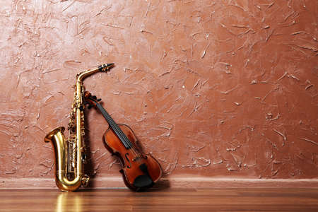Saxophone and violin on brown wall background Foto de archivo