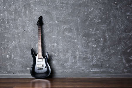 Electric guitar on gray wall background