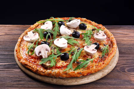 Tasty pizza with vegetables and arugula on black background