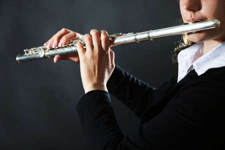 暗い背景でフルートを演奏するミュージシャン 写真素材 - 92986220