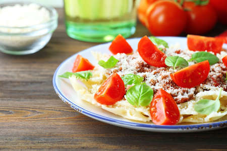 Pasta bolognese with cherry tomatoes in white plate on wooden table, closeup