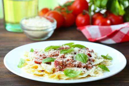 Pasta bolognese in white plate on wooden table, closeup Stock Photo