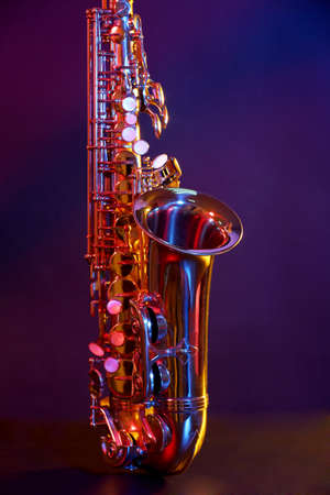 Golden saxophone on purple background