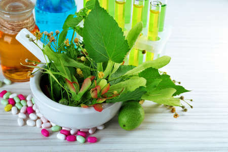 Herbs in mortar, test tubes and pills,  on table background 스톡 콘텐츠