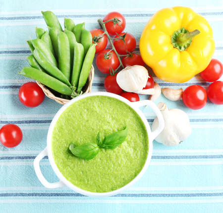 Tasty peas soup and vegetables on table close up Standard-Bild
