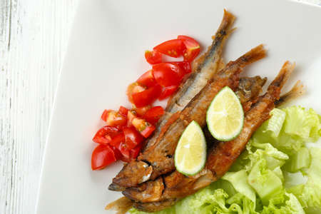Fried small fish with vegetables on table close up