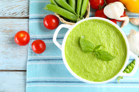 Tasty peas soup and vegetables on table close up Stock Photo