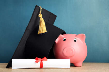 Piggy bank with grad hat and diploma on blackboard background