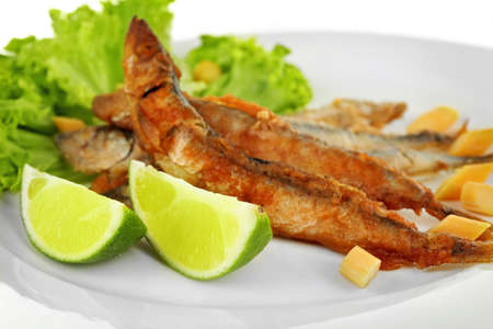 Fried small fish with lettuce and lime on plate close up