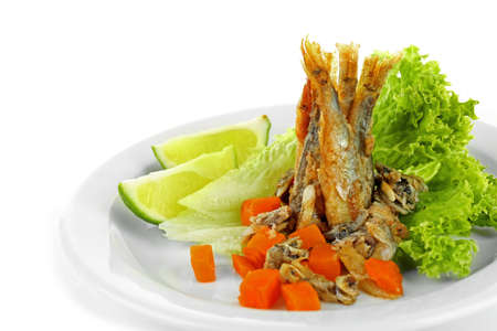 Fried small fish on plate with lettuce and lime isolated on white Stock Photo