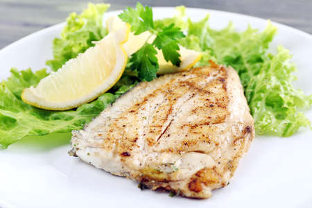 Dish of fish fillet with lettuce and lemon on plate close up Stock Photo