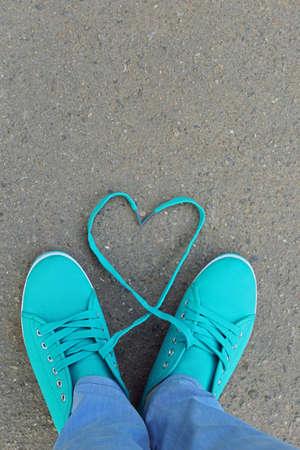 Female feet in gum shoes on asphalt background
