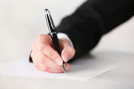 Female hand with pen writing on paper at workplace