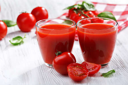 Glasses of tomato juice on wooden table, closeup Stock Photo