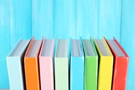 Colorful books on turquoise wooden background Stock Photo