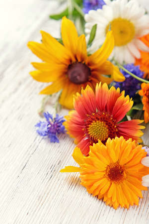 Bright wildflowers on wooden table, closeup