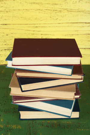 Stack of books on yellow wooden background