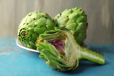 Artichokes on color wooden background Stock Photo