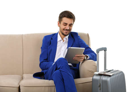 Business man with suitcase and tablet sitting on sofa isolated on white