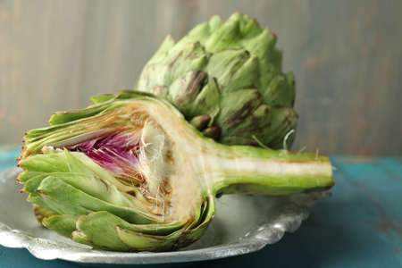 Artichokes on tray, on color wooden background