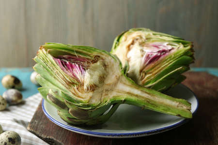 Artichokes on plate, on color wooden background Stockfoto