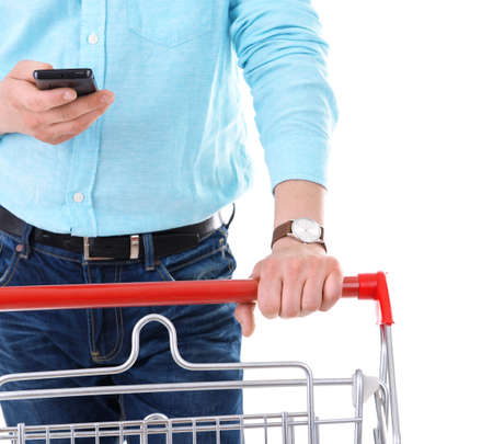 Young man holding mobile phone and shopping cart isolated on white Stock Photo
