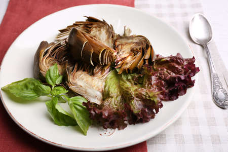 Roasted artichokes on plate, on kitchen table background