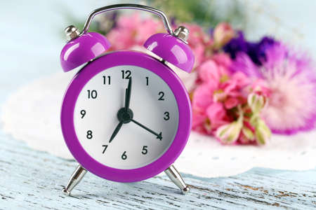 Small alarm clock with beautiful flowers on table close up