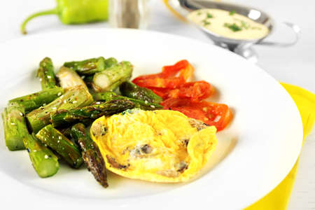 Roasted asparagus with fried egg on plate on table, close-up