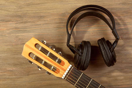Music recording scene with classical guitar and headphones on wooden background