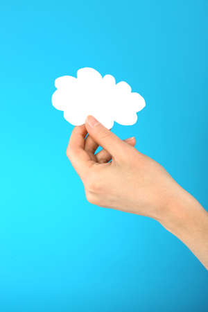 Hand holding paper cloud on blue background. Cloud computing concept. Stock Photo