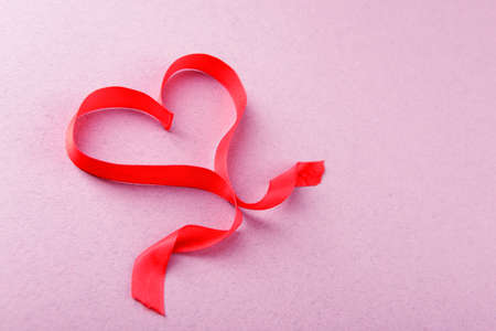 Red ribbon in shape of heart on light textured background