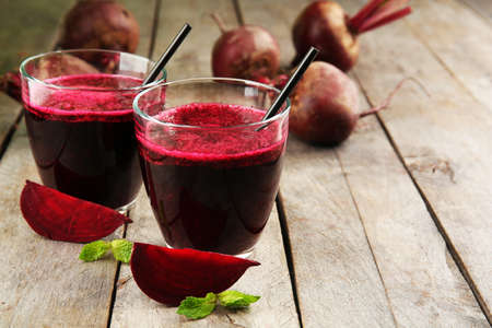 Glass of beet juice on wooden table, closeup Stock fotó