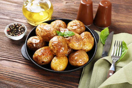 Baked potatoes in pan on wooden table, closeup
