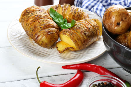 Baked potatoes on wooden table, closeup