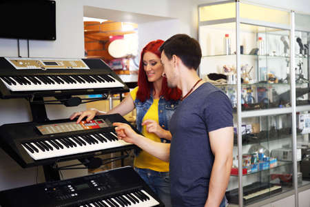 Beautiful young couple in music store Stock fotó
