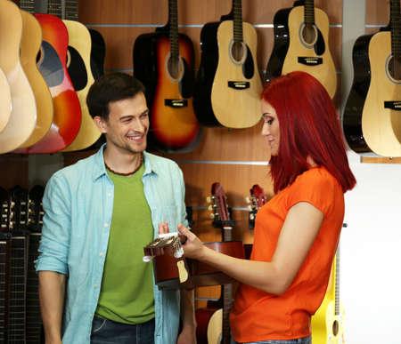 Beautiful young couple in music store Фото со стока